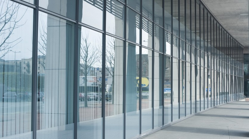 Modern commercial building interior with a view through the glass wall of the foyer to an urban environment